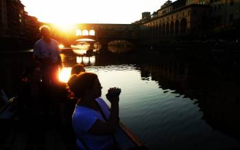 fall in love with florence living the magic of the sunset light and the golden reflections on the calm water of the Arno river